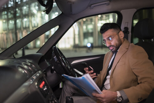 Businessman with smart phone reading paperwork in car at night - CAIF22006