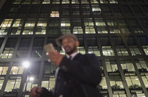 Businessman using smart phone below urban highrise at night - CAIF22015