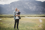 Portrait father and baby son standing in rural field - CAIF22027