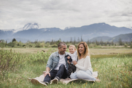 Parents and baby son sitting in rural field with mountains in background - CAIF22036