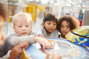 Curious kids at interactive globe exhibit in science center - CAIF22042