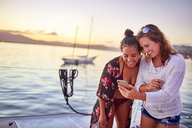 Young women friends using smart phone on boat - CAIF22108
