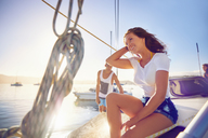 Happy young woman relaxing on sunny boat - CAIF22123