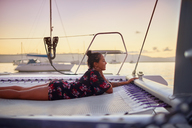 Serene young woman relaxing on catamaran net at sunset - CAIF22126