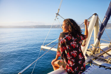 Serene young woman relaxing on sunny catamaran, looking out at blue ocean - CAIF22129
