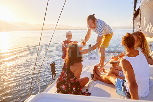 Friends relaxing, drinking champagne on sunny boat - CAIF22138