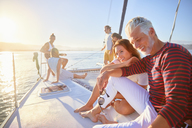 Friends relaxing on sunny catamaran - CAIF22141