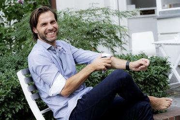Portrait of happy man sitting on chair in garden - HHLMF00368