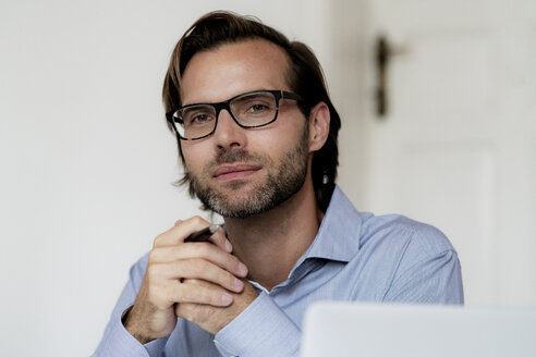 Portrait of confident man wearing glasses and holding pen - HHLMF00380