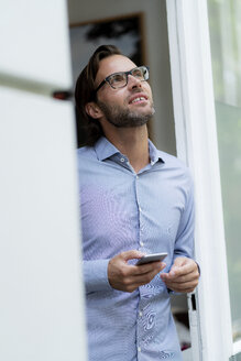 Confident man standing in doorframe holding cell phone looking up - HHLMF00383