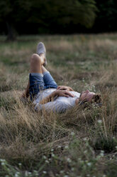 Relaxed man lying in field listening to music with headphones - HHLMF00386