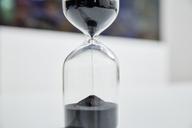 Black sand trickling through hourglass - RHF02109