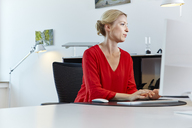 Young woman working on computer at desk in office - RHF02112
