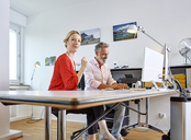 Two colleagues working together at desk in office - RHF02124