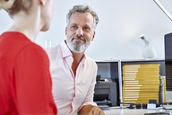 Mature man looking at female colleague at desk in office - RHF02127