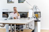 Portrait of smiling businessman sitting at desk in office - RHF02130