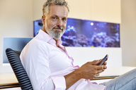 Portrait of confident businessman sitting in office using cell phone - RHF02136