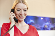 Portrait of smiling young woman on the phone in office - RHF02142