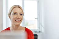 Portrait of smiling young woman in office - RHF02145