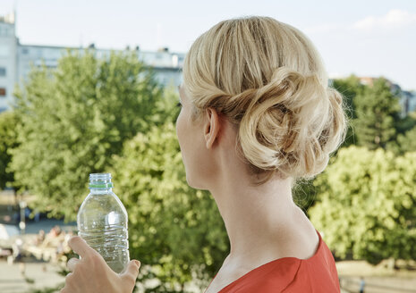 Rear view of young woman with water bottle - RHF02154