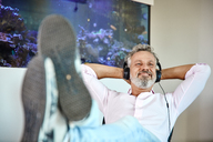 Relaxed mature man listening to music with headphones in front of aquarium - RHF02160