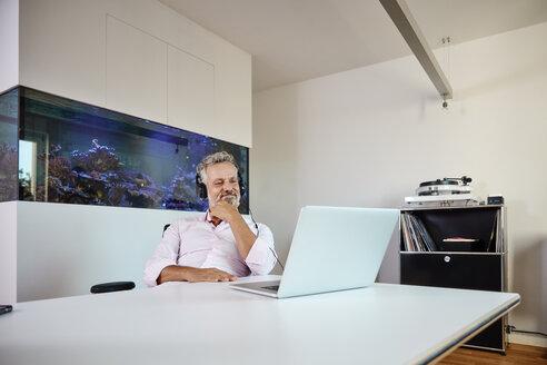 Businessman with headphones using laptop at desk in front of aquarium - RHF02163