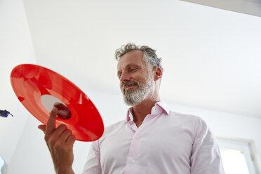 Smiling mature man holding red vinyl record - RHF02166