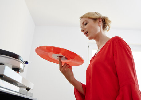 Young woman holding red vinyl record - RHF02169