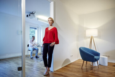 Portrait of young woman leaning against doorframe in office with colleague in background - RHF02187