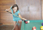 Young woman wearing green jumpsuit playing pool - LUXF00095