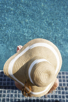 Woman wearing straw hat by swimming pool - LUXF00113