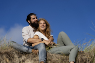 Young couple sitting on a dune in summer, relaxing - HHLMF00417