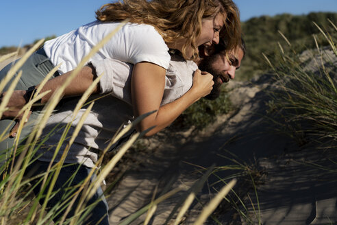 Young man carrying his girlfriend piggyback in the dunes - HHLMF00423