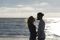 Young couple looking at each other, standing at the sea - HHLMF00441