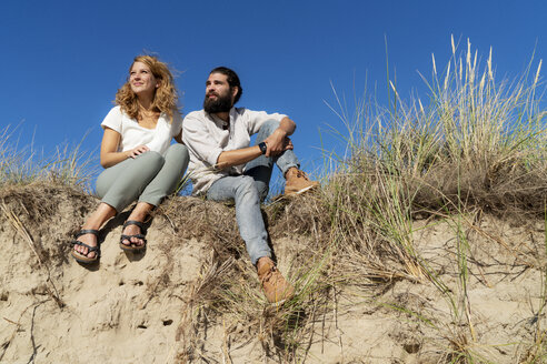 Young couple sitting on a dune in summer, relaxing - HHLMF00459