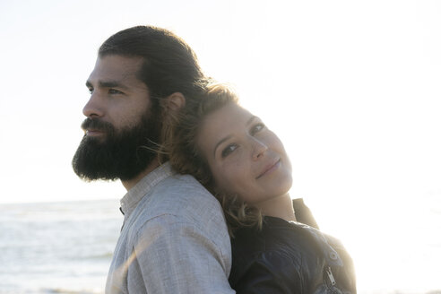 Young couple standing back to back at the sea - HHLMF00471