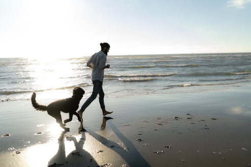 Young man running and playing with his dog on the beach - HHLMF00474