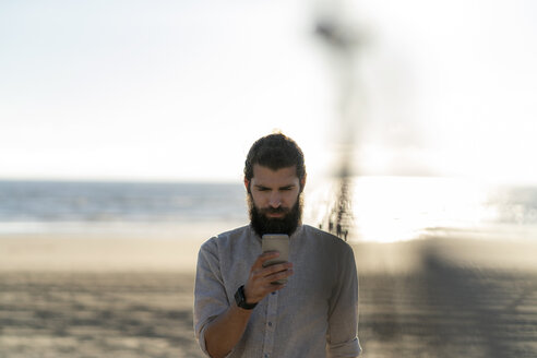 Young man using smartphone on the beach - HHLMF00477