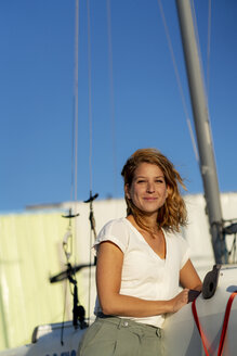 Portrait of a beautiful woman standing by a boat in summer - HHLMF00480