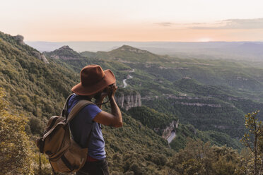 Spain, Barcelona, Montserrat, man with backpack taking photo of view at sunset - AFVF01552