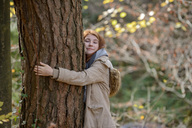 Portrait of smiling teenage girl hugging tree trunk in autumnal forest - LBF02045
