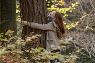 Happy teenage girl hugging tree trunk in autumnal forest - LBF02048