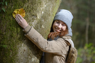 Portrait of smiling teenage girl hugging tree trunk in autumnal forest - LBF02051