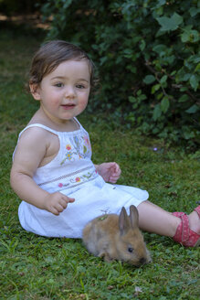 Portrait of content baby girl sitting on a meadow with young rabbit - LBF02057