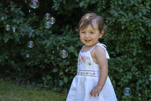 Portrait of smiling baby girl with soap bubbles in the garden - LBF02060