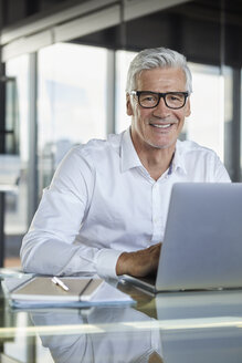 Businessman working in office, using laptop - RBF06582