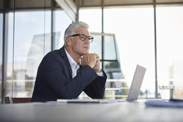 Businessman sitting in office, thinking - RBF06615