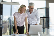Businessman and woman discussing project in office - RBF06627