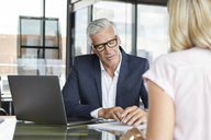 Businessman snd woman sitting in office, discussing project - RBF06636