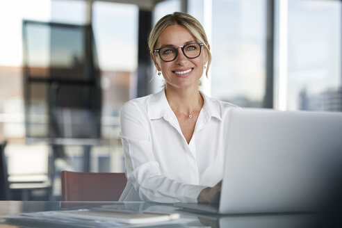 Businesswoman sitting at desk, using laptop, smiling friendly - RBF06639